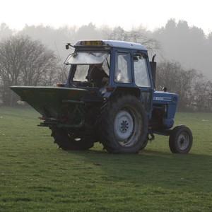 Ford tractor spreading fertiliser with a fertiliser spinner
