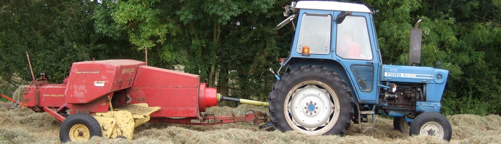 Ford tractor baling hay with New Holland baler